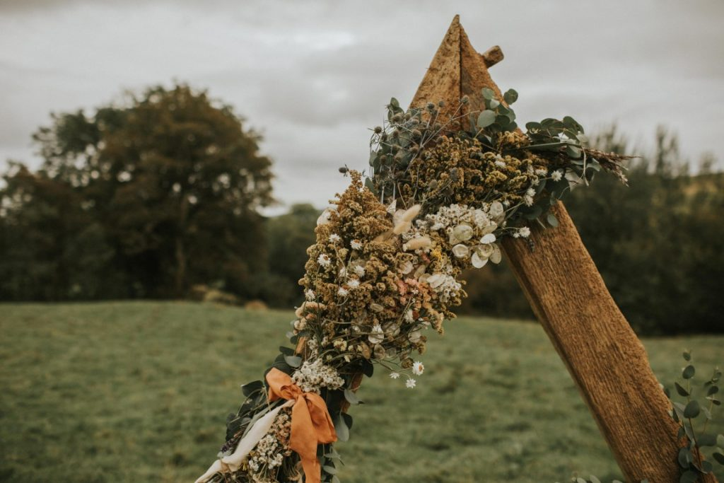 Dried flowers on arch for rustic ceremony on hilltop